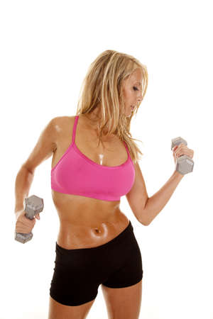 A woman working out with weights with sweat dripping off of her body. photo