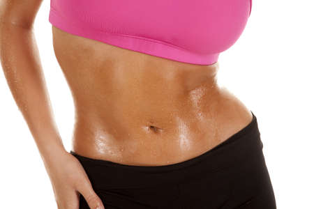 A woman's stomach and arm sweating after a workout. photo