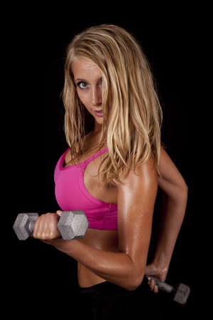A woman with sweat dripping off of her body working out with weights. photo
