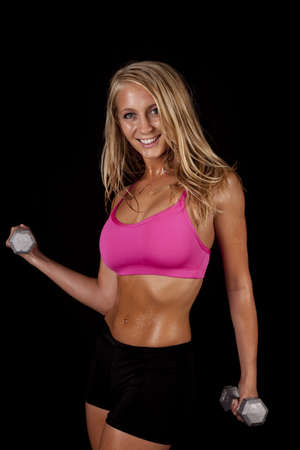 bra model: A woman working out with weights with sweat on her body and a smile on her face. Stock Photo