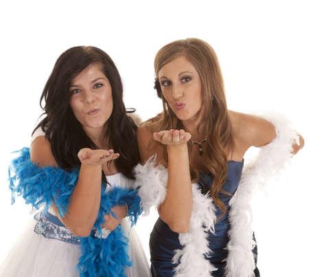 boas: Due ragazze adolescenti nei loro abiti da cerimonia e baci che soffia boa piumato per la fotocamera. Archivio Fotografico