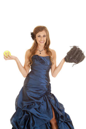 a teen girl in her blue formal dress holding up a softball and a mit. photo