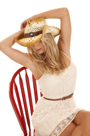 A woman sitting in a red chair in her lace dress wearing her cowgirl hat looking down. photo