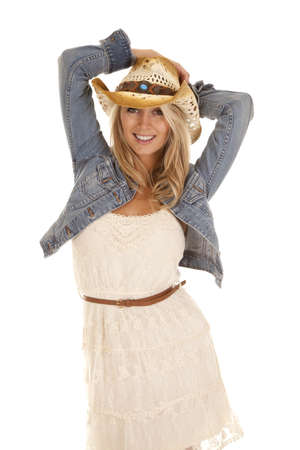 A woman standing with her hands on her hat in her denim jacket and lace dress with a smile on her face. Standard-Bild