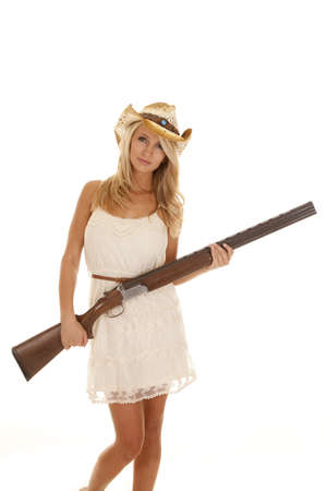 A woman in her lace dress holding on to her shot gun.