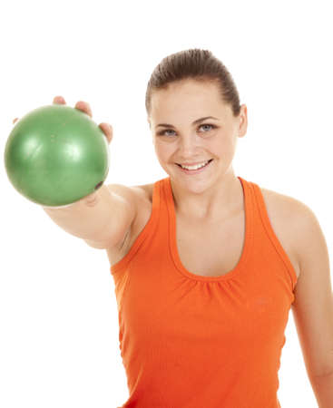weighted: a woman holding out her green weighted ball with a smile on her face.