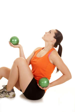 A woman sitting down on the ground working out with weighted balls with a serious expression on her face. Stock Photo - 15001944