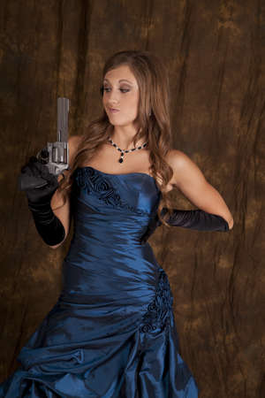 A teen girl in her formal dress holding a pistol with a funny expression on her face. photo
