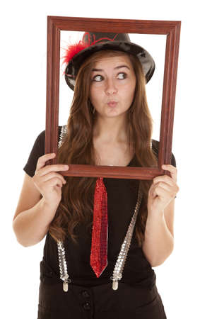 A teen girl showing her fun side by holding up a picture frame with a pucker on her lips. photo