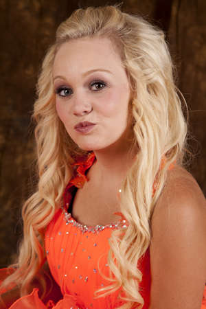 A young teen girl in her formal dress with her lips puckered up for a kiss. photo