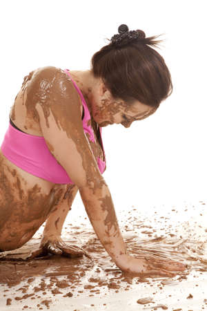 A woman pushing herself up in the mud.  Mud covering all over her body. photo