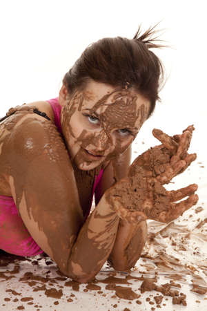 A close up of a womans arms, hands and face covered in mud. photo