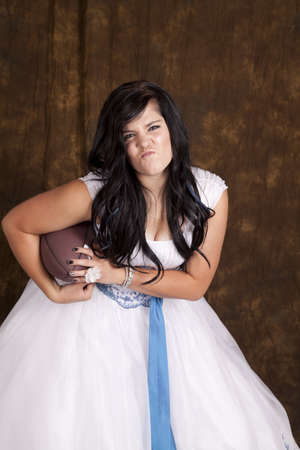 a teen girl in her formal dress holding on to a football with a funny expression, showing off her sporty side. photo