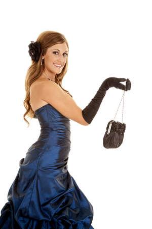 Een mooi tiener meisje houdt haar zwarte tas met haar handschoenen en een glimlach op haar gezicht.