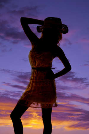 a silhouette of a cowgirl in her lace dress and cowgirl hat. Stock Photo