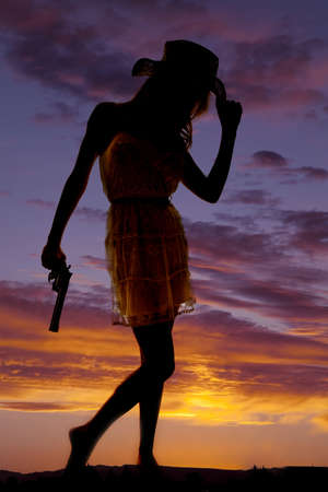 a silhouette of a woman holding on to her gun and holding on to the brim of her hat.