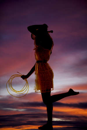 a silhouette of a woman standing with a rope in her hand and her foot up in the air. photo