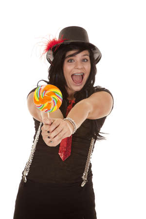 A teen girl in her jazzy outfit holding out a colorful sucker with a big smile on her face. photo