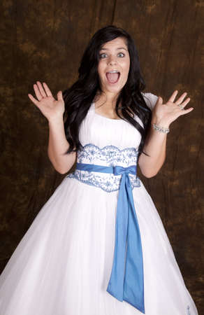 a teen girl in her white formal dress with a shocked expression on her face. photo