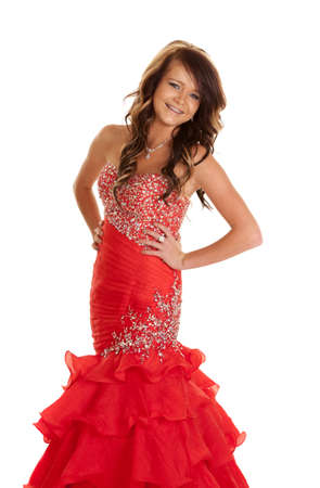 girl in red dress: A teen girl in her formal dress posing with a smile on her face.