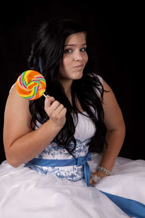 sucker: a teen girl with a funny expression on her face in her formal dress holding on to a colorful sucker