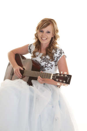 A teen girl in her formal dress sitting down with a smile on her face playing the guitar. photo
