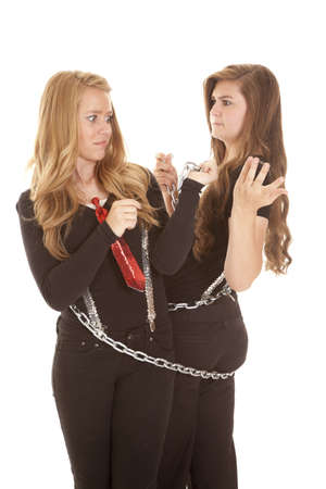 Two teen girls with funny expressions on their faces chained together