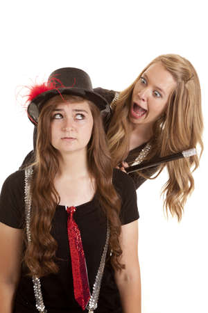 Two teen girls one is in a top hat and the other has a cane with silly expressions on their faces. photo