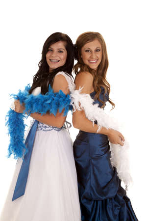 Two teen girl standing back to back in their formals and feathered boas with smiles on their faces.