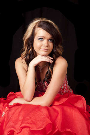 A teen girl sitting in her red dress with her hand under her chin looking peaceful. photo