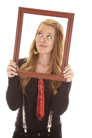 teen legs: A teen girl looking up holding on to a picture frame with a silly expression.