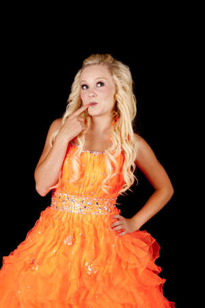 formal attire: a teen in her orange formal dress with a cute expression on her face