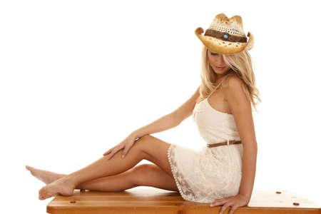 stile country: Una donna seduta su una panca di legno con le ginocchia guardando verso il basso Archivio Fotografico