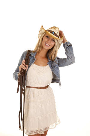 A woman  in her lace dress and denim jacket holding on to her bridle and hat with a smile on her face