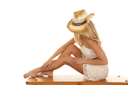 country style: A woman sitting on a wooden bench with her knees up looking down. Stock Photo