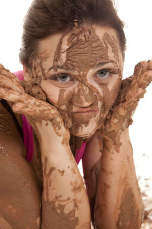 A close up of a womans face with mud all over her cheeks and hands. photo