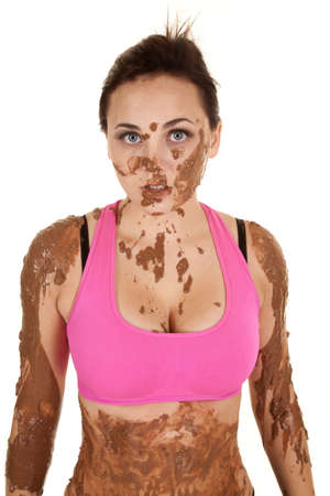 A woman's top half of her body covered in mud with a serious expression on her face.