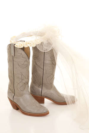 meaningful: A close up of a pair of cowboy boots with a wedding veil Stock Photo