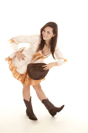 A woman showing off her western personality bowing in her cowgirl boots.