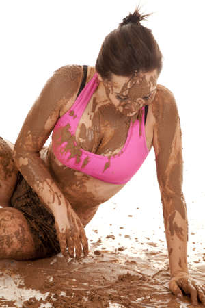 A woman sitting in a bunch of mud, with mud all over her body. photo