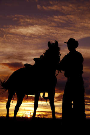 A cowboy is standing by his horse in the sunset. photo