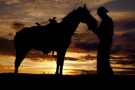 A cowboy is standing by his horse in the sunset holding its head.
