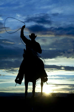 west country: A cowboy is riding forward in the sunset with a rope above his head.