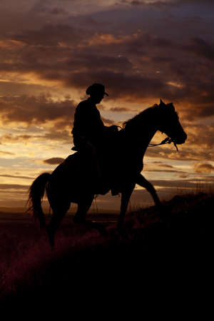 A cowboy is riding his horse up a hill in the sunset. photo