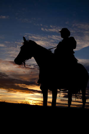 A cowboy is sitting on his horse in the sunset.