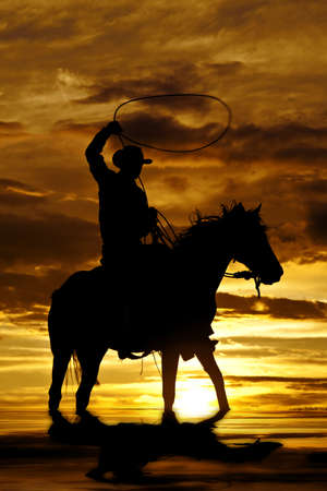 A cowboy is sitting on his horse in the sunset and swinging a rope standing in water.