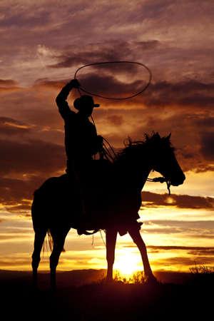 vaquero: Un vaquero est� sentado en su caballo en la puesta del sol y blandiendo una cuerda.