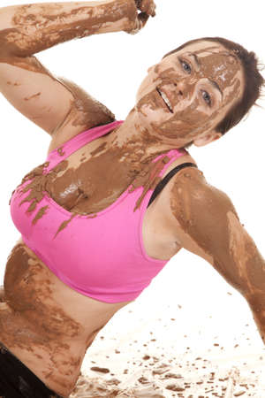 A woman with a playful expression on her face covered in mud photo