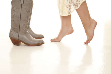 barefoot cowboy: A woman standing on her tip toes while her man is in his cowboy boots.