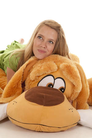 A teen girl laying on her stuffed dog with a smile on her face photo